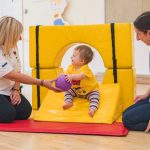 Tumble Tots baby passing ball to Leader